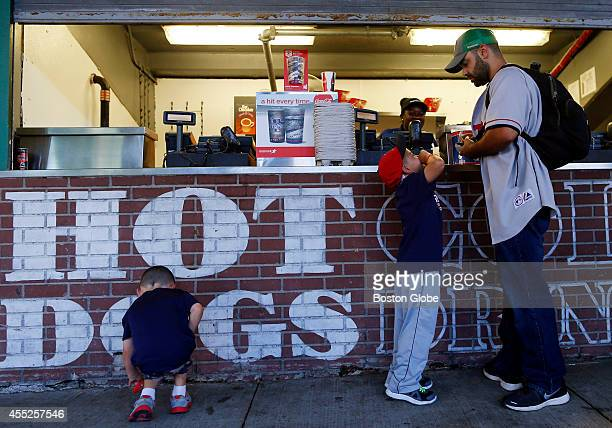 Right to left Peter Donnelly stops to buy hotdogs for his two sons Jack and Lucas as the three take in a game between the Boston Red Sox and the...