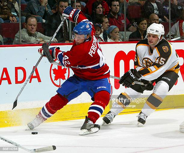 Right wing Alexander Perezhogin of the Montreal Canadiens battles for the puck against defenseman Mark Stewart of the Boston Bruins during a...
