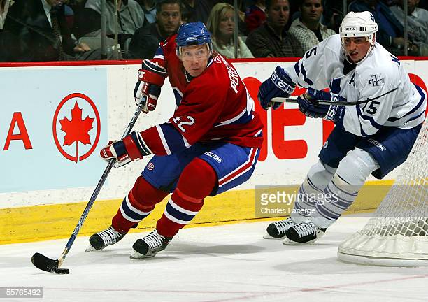 Right wing Alexander Perezhogin of the Montreal Canadiens carries the puck against defenseman Tomas Kaberle of the Toronto Maple Leafs during a...