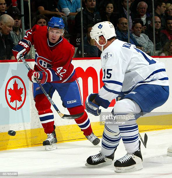Right wing Alexander Perezhogin of the Montreal Canadiens plays the puck against defenseman Tomas Kaberle of the Toronto Maple Leafs during a...