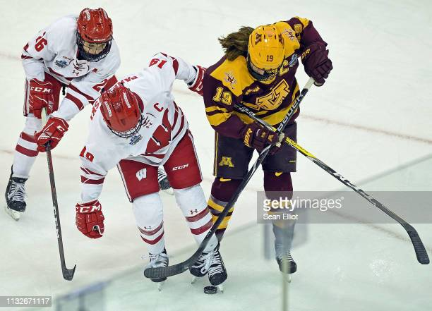 Right wing Annie Pankowski and center Emily Clark of the Wisconsin Badgers battle center Kelly Pannek of the Minnesota Golden Gophers for the puck...