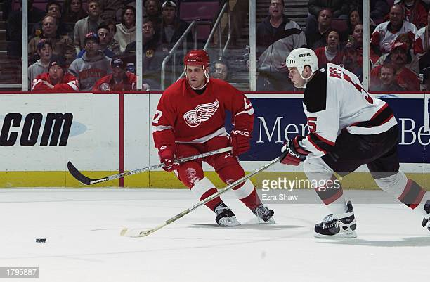 Right wing Brett Hull of the Detroit Red Wings and defenseman Colin White the New Jersey Devils go after the puck during the NHL game at Continental...