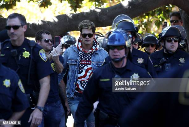 Right wing commentator Milo Yiannopoulos is escorted by police officers after he spoke during a free speech rally at U.C. Berkeley on September 24,...