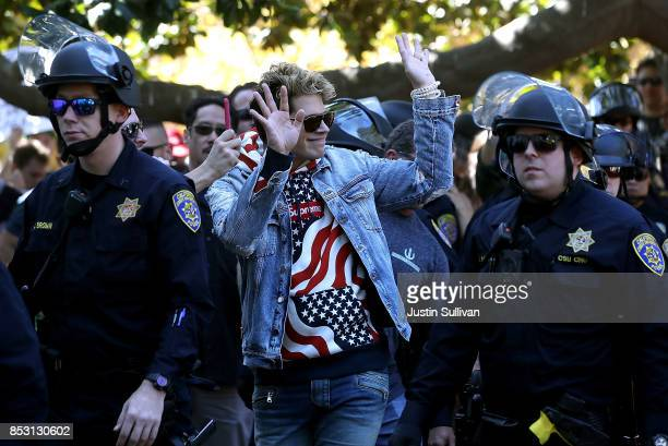 Right wing commentator Milo Yiannopoulos is escorted by police officers after he spoke during a free speech rally at UC Berkeley on September 24 2017...