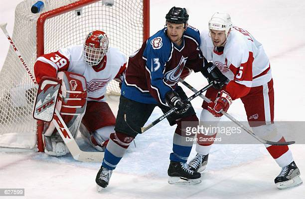 Right wing Dan Hinote of the Colorado Avalanche jostles in the crease with defenseman Nicklas Lidstrom of the Detroit Red Wings in front of...