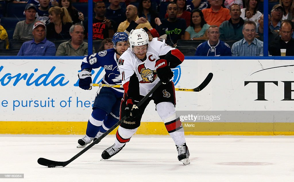 Right wing Daniel Alfredsson #11 of the Ottawa Senators advances the puck as right wing Martin St. Louis #26 of the Tampa Bay Lightning pursues during the game at the Tampa Bay Times Forum on April 9, 2013 in Tampa, Florida.