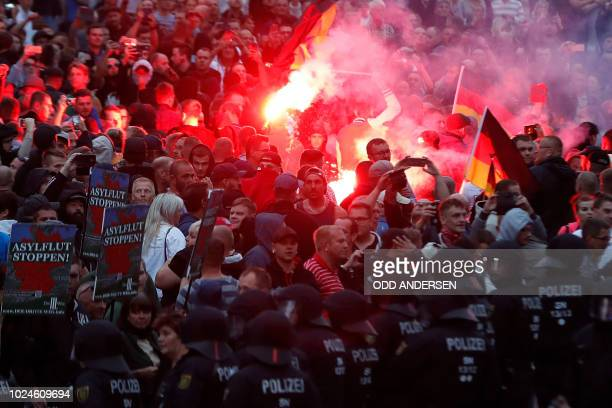 Right wing demonstrators light flares on August 27, 2018 in Chemnitz, eastern Germany, following the death of a 35-year-old German national who died...