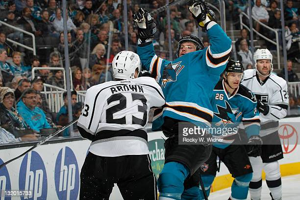 Right wing Dustin Brown of the Los Angeles Kings collides with defenseman Colin White of the San Jose Sharks at the HP Pavilion on November 7 2011 in...