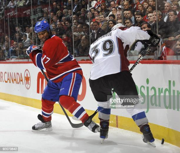 Right Wing Georges Laraque of the Montreal Canadiens battles for the puck possession against TJ Galiardi of the Colorado Avalanche during the NHL...
