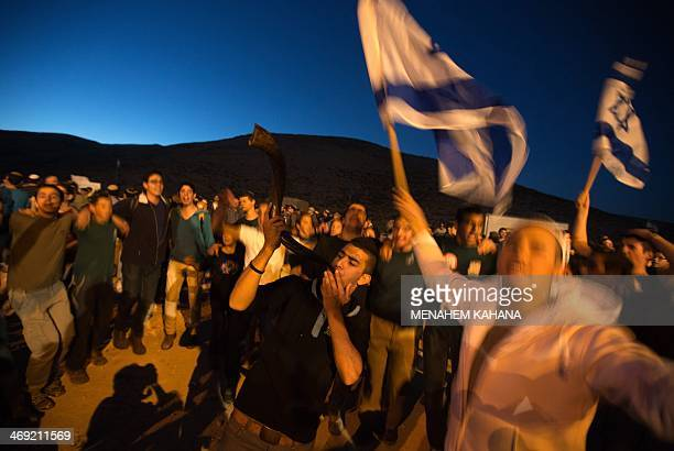 Right wing Israelis wave the national flag and dance during a march from the Jewish settlement of Maale Adumim to the controversial West Bank area...