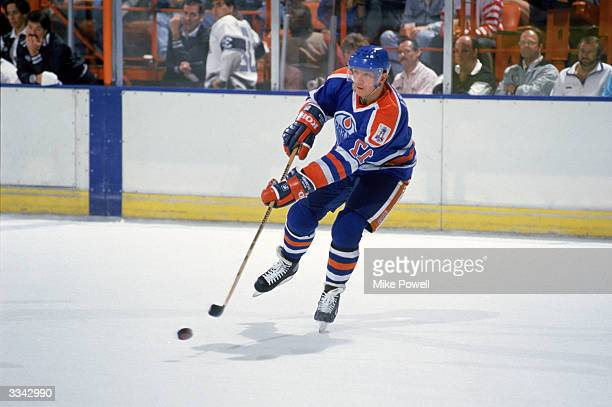 Right wing Jari Kurri of the Edmonton Oilers passes the puck against the Los Angeles Kings during the 198990 season at the Great Western Forum in...