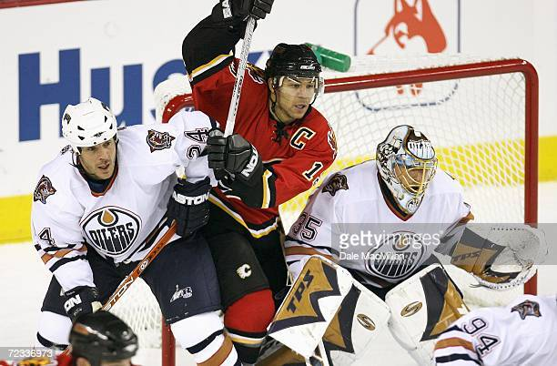Right wing Jarome Iginla of the Calgary Flames jockeys for goal position between defenseman Steve Staios and goaltender of Dwayne Roloson the...