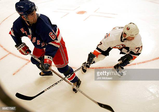 Right wing Jaromir Jagr of the New York Rangers plays the puck away from defenseman Alexei Zhitnik of the New York Islanders during their pre-season...