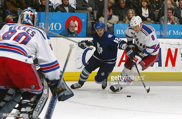 Right wing Jeff O'Neill of the Toronto Maple Leafs battles for the puck with defenseman Marek Malik of the New York Rangers as goaltender Kevin...