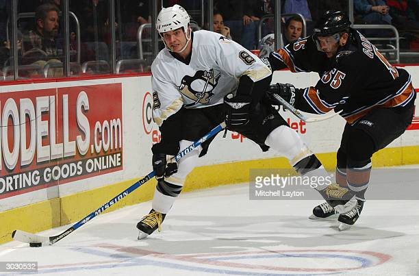 Right wing Matt Bradley of the Pittsburgh Pengiuns skates on the ice by defenseman Sergei Gonchar of the Washington Capitals during the game on...