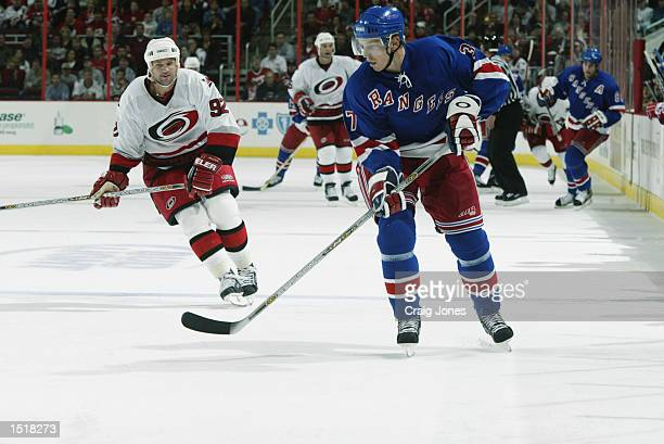 Right wing Mikael Samuelsson of the New York Rangers carries the puck into the zone while being pursued by Jeff O'Neill of the Carolina Hurricanes on...
