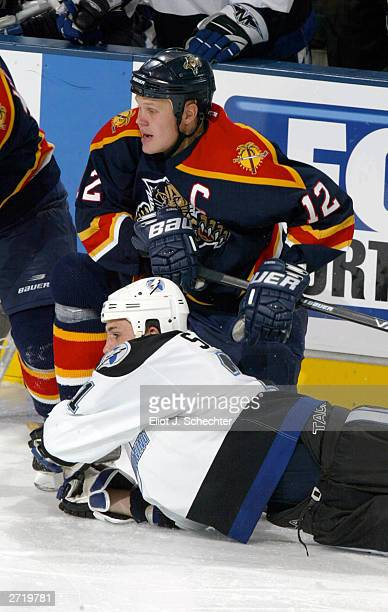 Right wing Olli Jokinen of the Florida Panthers knocks Defender Cory Sarich of the Tampa Bay Lightning to the ice in NHL action on November 11, 2003...