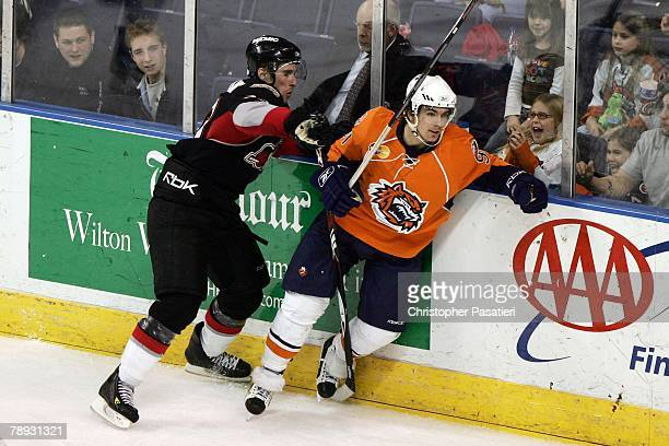 Right wing Pierre LucFaubert of the Bridgeport Sound Tigers is checked by defenseman Brett Festerling of the Portland Pirates during the NHL game on...