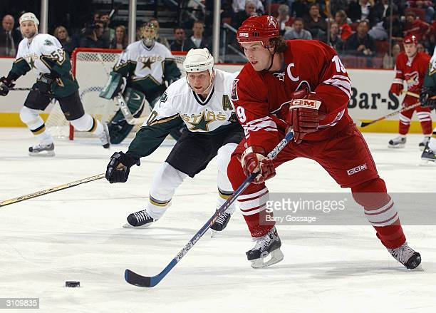 Right wing Shane Doan of the Phoenix Coyotes moves the puck against Brenden Morrow of the Dallas Stars during the game on February 14 2004 at...