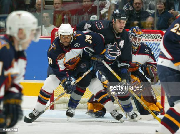 Right wing Todd Bertuzzi of the Vancouver Canucks battles with right wing Jean-Luc Grand-Pierre of the Atlanta Thrashers during their game at General...