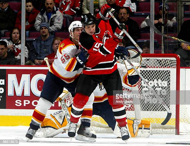 Right winger Jamie Langenbrunner of the New Jersey Devils attempts to deflect a shot with his stick as defenseman Sean Hill of the Florida Panthers...