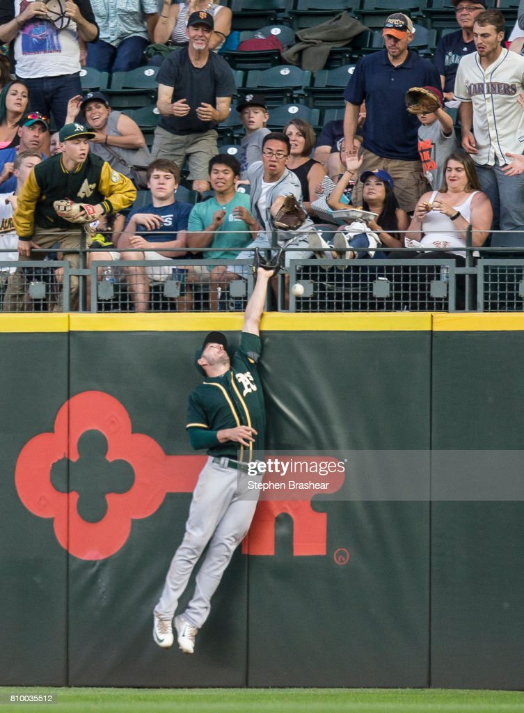 Rightfielder Matt Joyce #23 of the Oakland Athletics jumps at the outfield wall attempting to catch a home run hit by Mitch Haniger #17 of the Seattle Mariners off of starting pitcher Paul Blackburn #58 of the Oakland Athletics during the fifth inning of game at Safeco Field on July 6, 2017 in Seattle, Washington. The Athletics won 7-4.