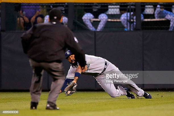 Rightfielder Matt Kemp of the San Diego Padres dives to make a catch on a soft line drive by Carlos Gonzalez of the Colorado Rockies as umpire Gabe...
