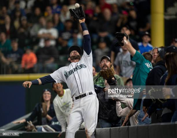 Rightfielder Mitch Haniger of the Seattle Mariners catches ball hit by Jose Iglesias of the Detroit Tigers before falling over the fence in foul...