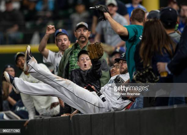Rightfielder Mitch Haniger of the Seattle Mariners falls into the stands after catching a ball hit by Jose Iglesias of the Detroit Tigers during the...