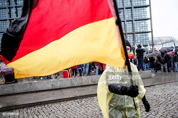 A rightwing activist holds the German National flag as he and others gather in front of Hauptbahnhof main railway station before marching through the...