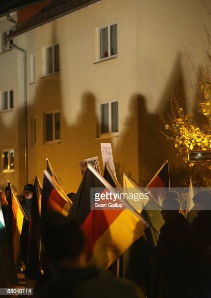 Rightwing activists carrying German and Saxon flags and chanting Wir sind das Volk cast shadows onto a nearby apartment building as they gather to...
