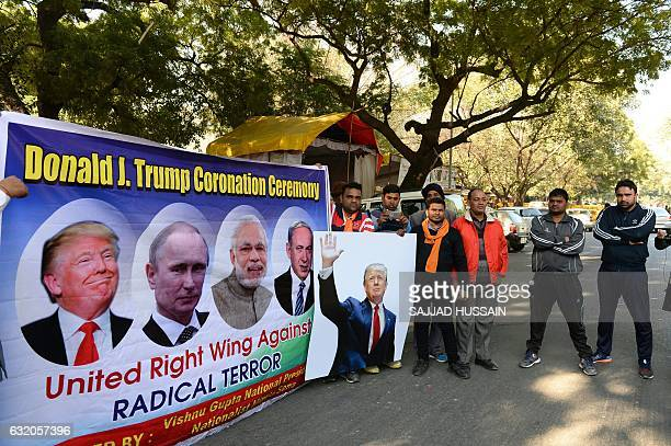 Rightwing activists of India's Hindu Sena party pose with a poster of US Presidentelect Donald Trump Russian President Vladimir Putin and Indian...