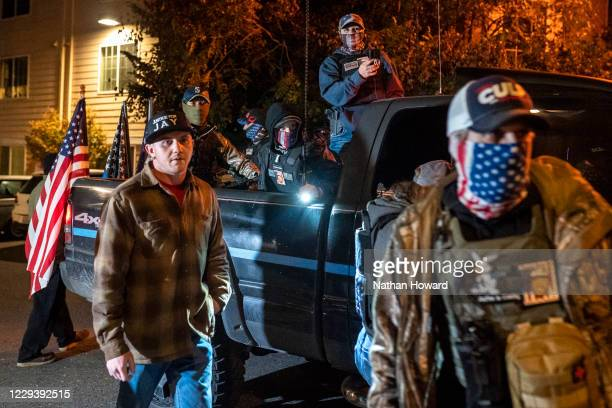 Right-wing activists retreat to a truck while arguing with Black Lives Matter protesters on October 31, 2020 in Vancouver, Washington. Dueling...