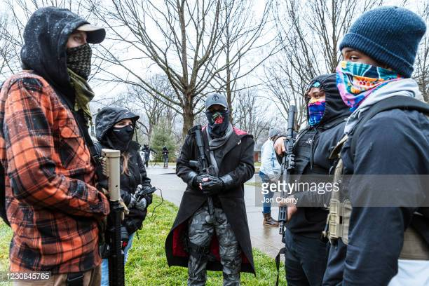 Right-wing and left-wing members of the armed militia known as the Boogaloo Boys converse near the Capitol Building on January 17, 2021 in Frankfort,...