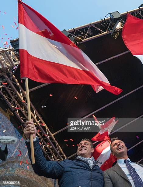 Rightwing Austrian Freedom Party presidential candidate Norbert Hofer and Leader of the FPOe HeinzChristian Strache wave flags on stage during...