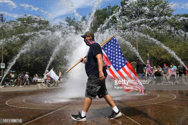 Right-wing demonstrator carries an American flag during rally on August 4, 2018 in Portland, Oregon. The rally was organized by the group Patriot...