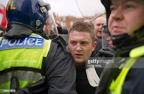 Rightwing EDL founder Stephen Lennon passes between police officers during a rally in Luton Hertfordshire on February 5 2011 AFP PHOTO/LEON NEAL