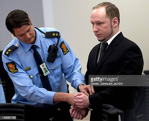 Rightwing extremist Anders Behring Breivik stands handcuffed in front of a police officer as he arrives in room 250 of the central court in Oslo in...