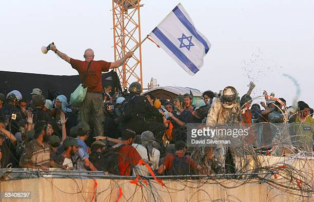 Rightwing Israeli activist leader Colonel Moshe Leshem waves the Israeli flag as Israeli riot police break onto the synagogue roof where hundreds of...
