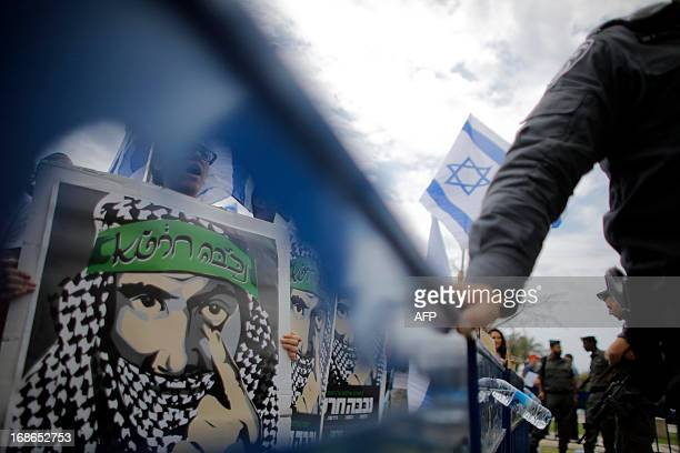Right-wing Israeli activists hold up a posters showing a man wearing the traditional Arab Keffiyeh during a rally denouncing Nakba day in Tel Aviv...