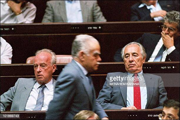 Right-wing Israeli Premier Yitzhak Shamir walks 07 May 1990 in Jerusalem past Knesset members and Labour party leaders Yitzhak Rabin and Shimon Peres...