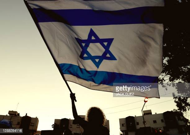 Right-wing Israeli supporters of Prime Minister Benjamin Netanyahu chant slogans and wave the national flag during a demonstration against the...