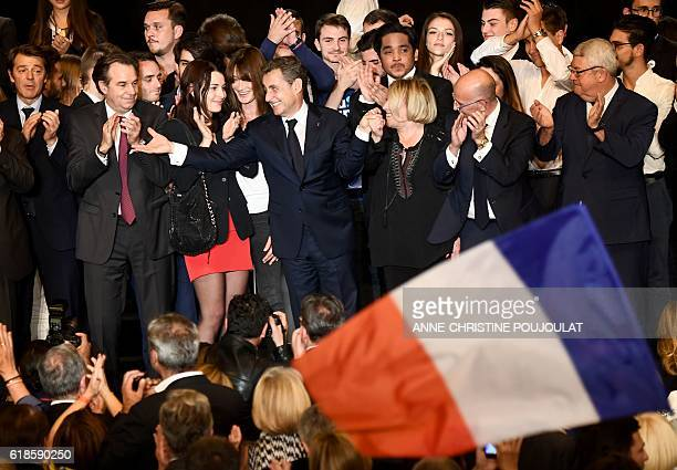 Rightwing Les Republicains party's candidate for the party's primary ahead of the 2017 presidential election Nicolas Sarkozy gestures next to his...