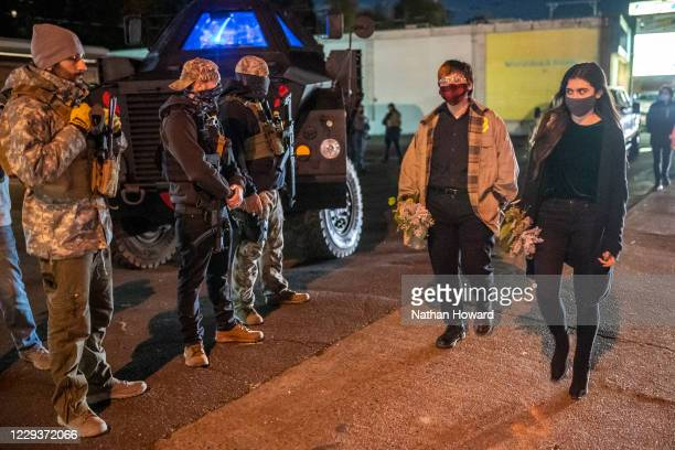 Right-wing militia members guard a private business as Black Lives Matter activists walk to a vigil for Kevin E. Peterson Jr., on October 30, 2020 in...