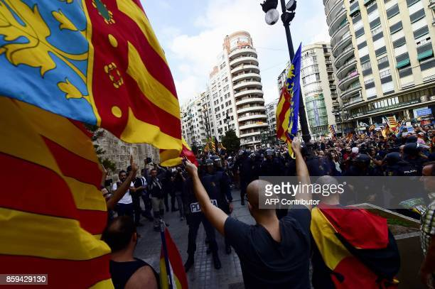 A rightwing nationalist waves Valencia City flags opposite Spanish police forces separating nationalists from a counter demonstration in support of...