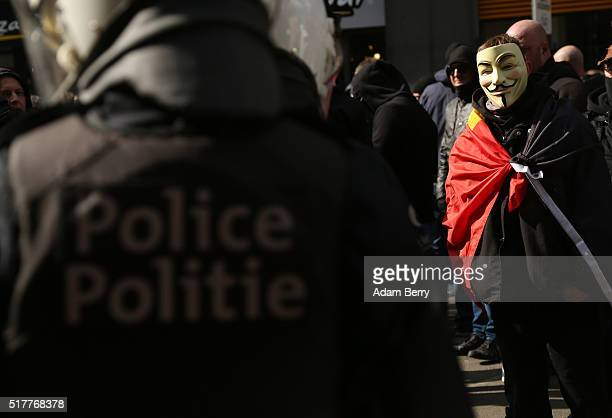 A rightwing selfdescribed hooligan in a Guy Fawkes mask demonstrates on Place de la Bourse on March 27 in Brussels Belgium Days after suicide bomber...