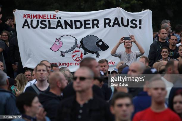 """Right-wing supporters hold a banner that reads """"Criminal Foreigners Out"""" at a right-wing protest gathering the day after a man was stabbed and died..."""