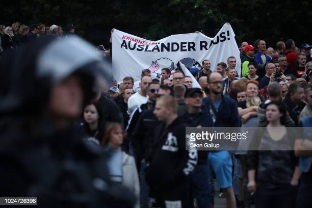 "Right-wing supporters hold a banner that reads ""Criminal Foreigners Out"" at a right-wing protest gathering the day after a man was stabbed and died..."