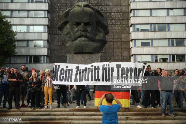 Rightwing supporters hold a banner that reads No Access for Terror next to a monument to Karl Marx at a rightwing protest gathering the day after a...