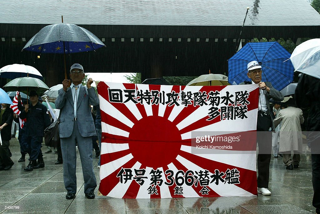 Right-wingers carry Japanese sun flags outside the Yasukuni War Shrine August 15, 2003 in Tokyo, Japan. Today marks the 58th anniversay of Japan's surrender at the end of World War II.